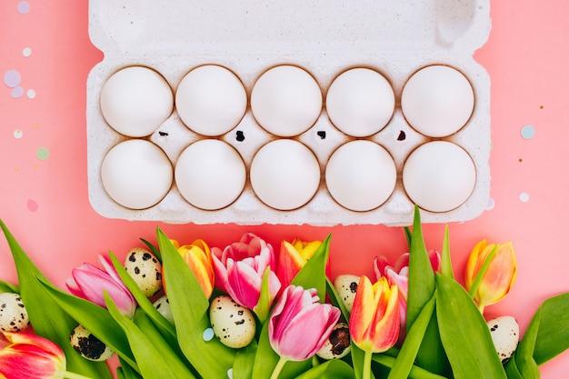 Concept de pâques, plats pondent des œufs de poule et des confettis vibrants, des tulipes multicolores et des œufs de caille sur fond rose.