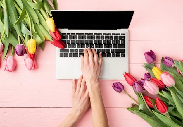 Concept de pâques et de printemps. mains de femme tapant sur le clavier de l'ordinateur portable. espace de travail féminin décoré de tulipes