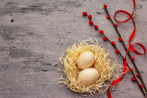 Concept de pâques zéro déchet. oeuf en bois, nid d'oiseau, ruban de satin, phoques de saule rouge. pas de plastique, tendance écologique. fond béton gris