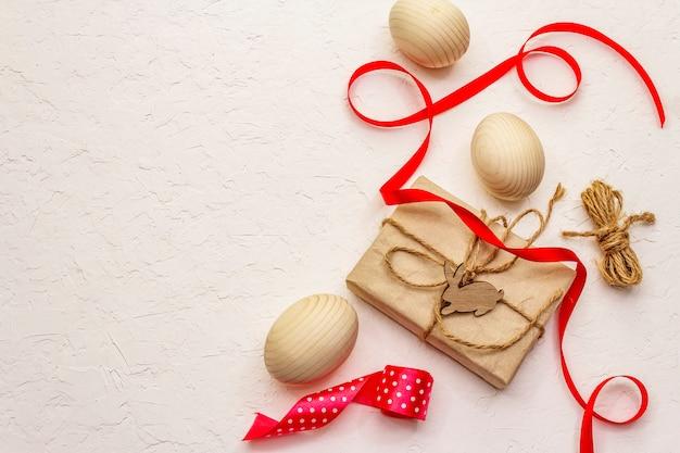 Concept de pâques zéro déchet. oeufs en bois, cadeaux en papier kraft. pas en plastique, tendance écologique. fond de mastic blanc