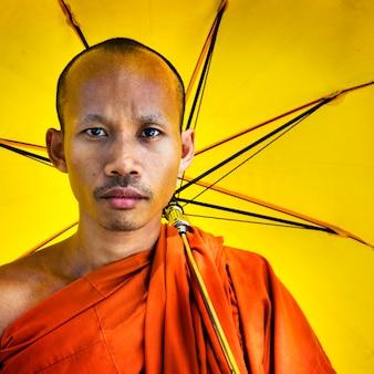 Concept de parapluie tenant moine bouddhiste