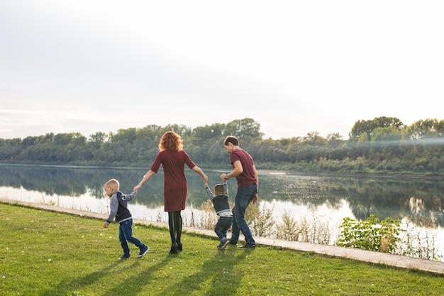 Concept parent, enfance et nature - famille jouant avec deux fils au bord de l'eau.
