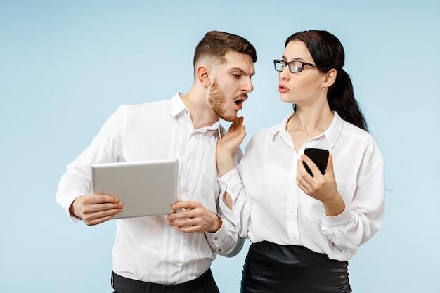 Concept de partenariat en entreprise. jeune homme et femme émotionnelle contre le mur bleu à. concept d'émotions humaines et de partenariat