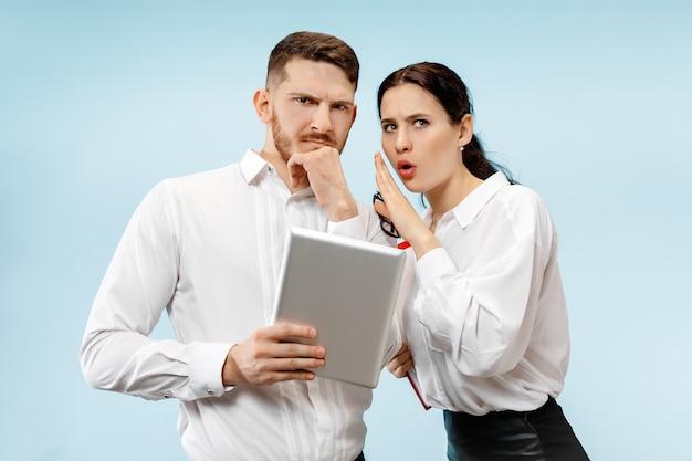 Concept de partenariat en entreprise. jeune homme et femme à la recherche suspecte contre le mur bleu