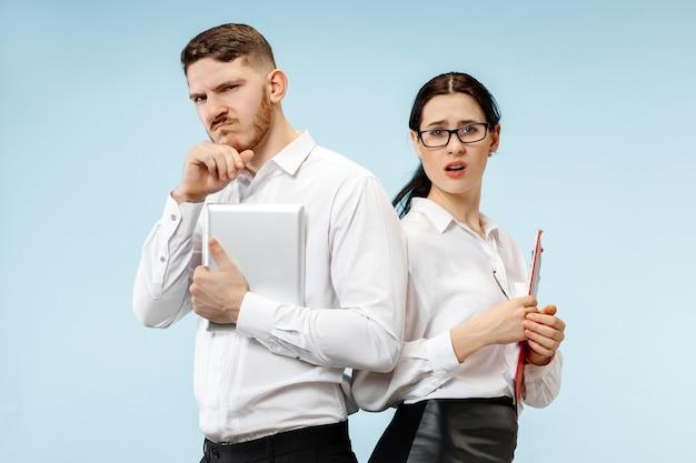 Concept de partenariat en entreprise. jeune homme et femme à la recherche suspecte sur fond bleu au studio