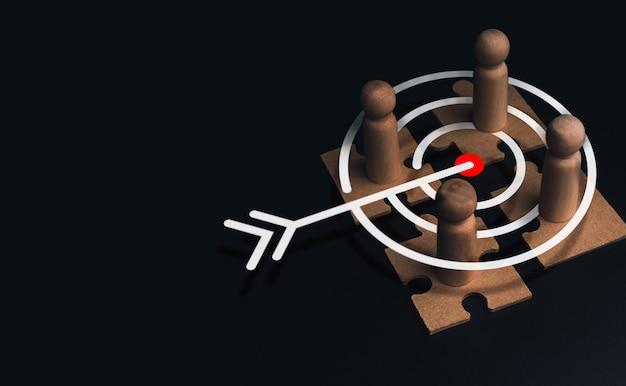 Concept de partie prenante, de connexion d'affaires, de travail d'équipe et de consolidation d'équipe. figure en bois en gros plan, en tant qu'homme d'affaires sur des puzzles avec symbole d'icône cible sur fond sombre avec espace de copie.