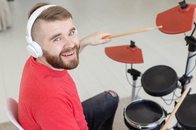 Concept de passe-temps, de musique et de personnes - homme batteur sur le mur de lumière