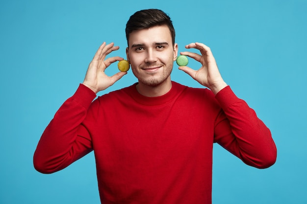 Concept de pâtisserie, de pâtisserie et de personnes. image horizontale de beau jeune homme élégant à la recherche amicale