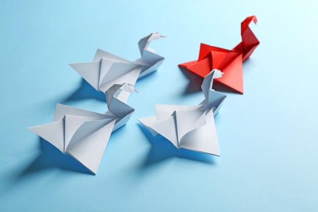 Concept de patron contre leader. oiseaux blancs d'origami derrière un rouge sur le fond bleu