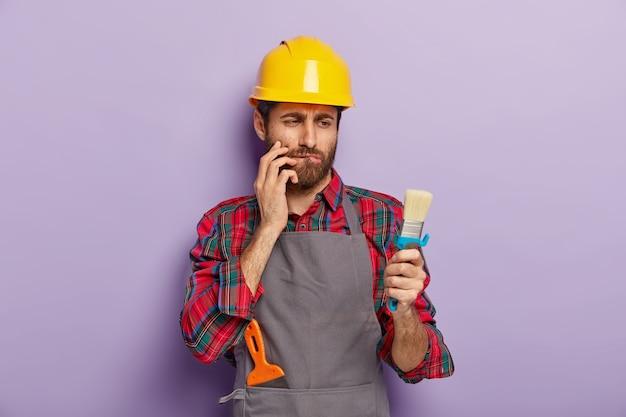 Concept de peinture murale. artisan sérieux et attentionné regarde une brosse propre, mord la lèvre inférieure, pense comment commencer la rénovation de son appartement, porte un couvre-chef et un tablier jaune, isolé sur un mur violet