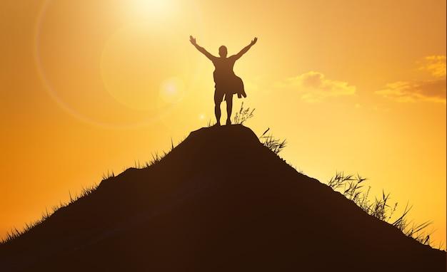 Concept de personnes d'affaires et de succès, de leadership et de réussite. silhouette d'homme au sommet de la montagne sur fond de ciel coucher de soleil. photo mains en l'air
