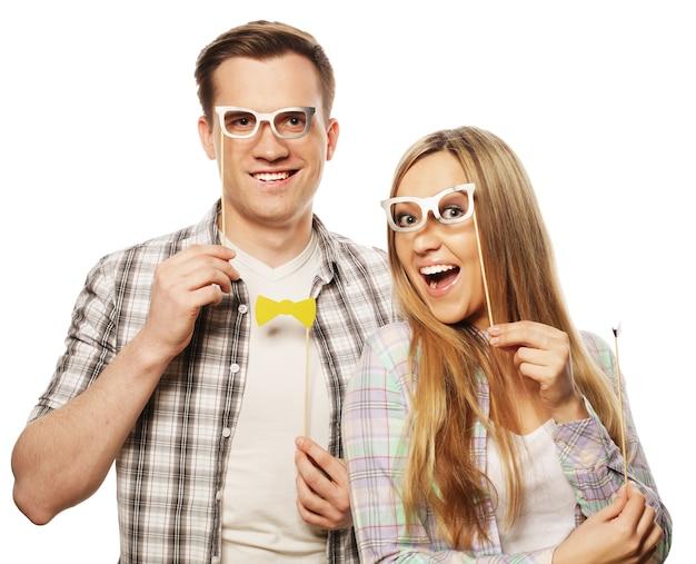 Concept de personnes, d'amitié, d'amour et de loisirs - joli couple tenant des lunettes de fête sur un bâton