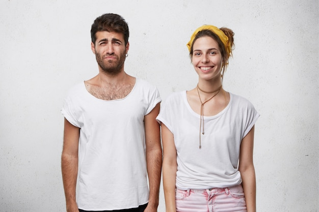 Concept de personnes, d'amour et de relations. homme européen barbu pleurant, se sentant triste et malheureux alors qu'il doit faire du shopping avec sa belle femme qui se tient à côté de lui avec un regard heureux