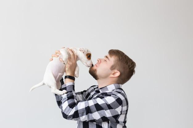 Concept de personnes, d'animaux et d'animaux - gros plan sur un jeune homme tenant un chiot jack russell terrier sur fond blanc.