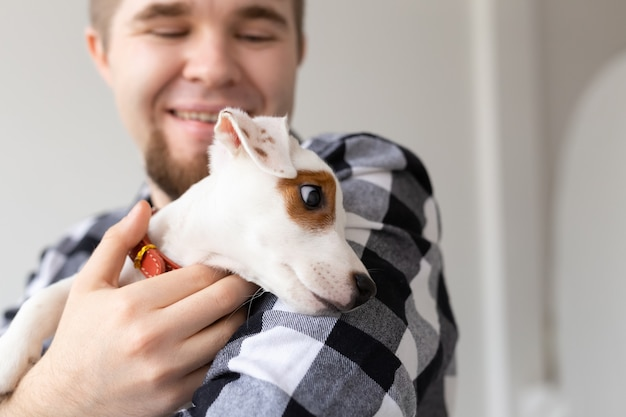 Concept de personnes, d'animaux et d'animaux - gros plan sur un jeune homme tenant un chiot jack russell terrier.