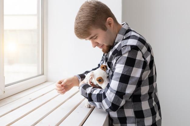 Concept de personnes, d'animaux et d'animaux - jeune homme étreignant le chiot jack russell terrier