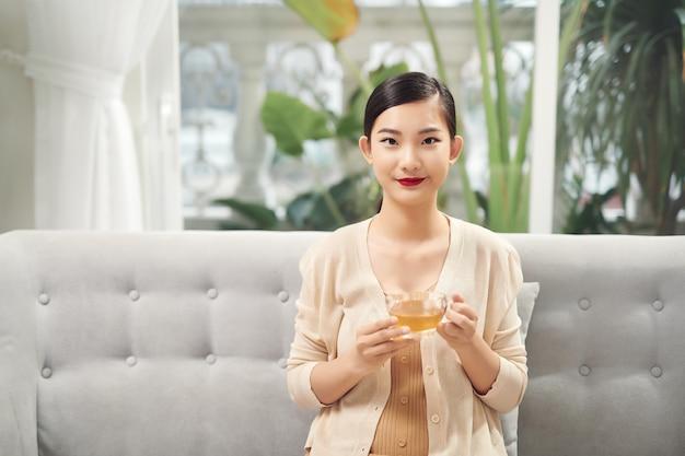 Concept de personnes, de boissons et de loisirs - jeune femme heureuse avec une tasse de thé à la maison