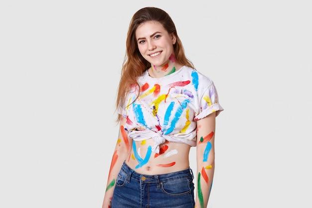 Concept de personnes, de créativité et d'art. un modèle féminin positif peint à l'aquarelle, vêtu d'un haut décontracté et d'un jean, isolé sur blanc, sourit joyeusement. femme creats photo