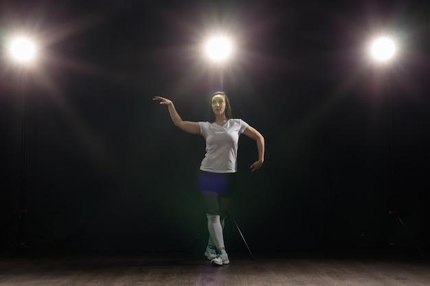 Concept de personnes et de danse - jolie femme dansant jazz funk sur fond sombre.
