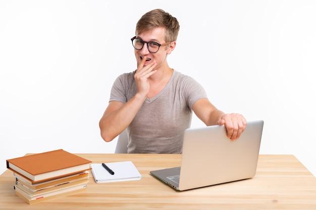 Concept de personnes et d'éducation - homme étudiant drôle assis à la table en bois avec ordinateur portable et livres