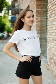 Concept de personnes, émotions, nature, beauté et style de vie -gros plan portrait de femme de mode d'une jeune fille assez tendance posant dans la ville, mode de rue d'été, portrait riant et souriant. branché