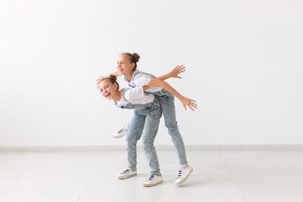 Concept de personnes, d'enfants et de famille - petite fille portant sa sœur jumelle sur fond blanc.