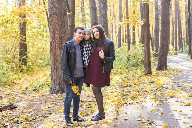 Concept de personnes, de famille et de loisirs - famille heureuse avec fille marchant dans le parc en automne.