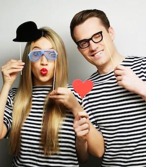 Concept de personnes, de fête, d'amour et de loisirs - joli couple tenant des lunettes de fête et un chapeau sur des bâtons, sur une surface grise