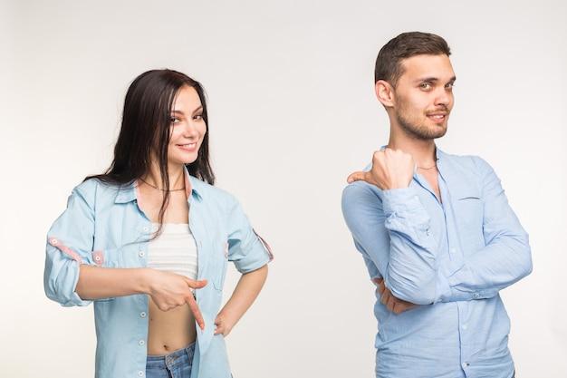 Concept de personnes et de geste. jeune jolie femme et bel homme pointant vers le bas sur fond blanc