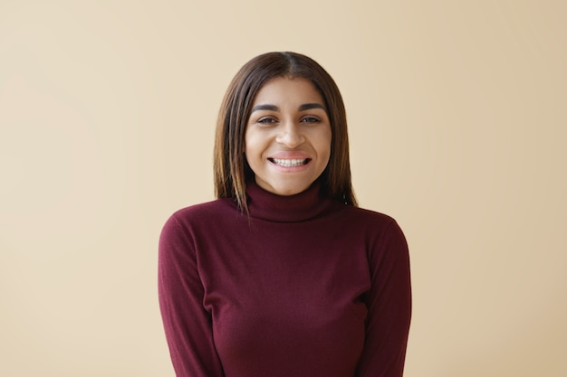 Concept de personnes, de joie et de bonheur. horizontal heureux joyeux à la mode jeune femme afro-américaine brune souriant largement, se sentir heureux après de bons achats dans la vente