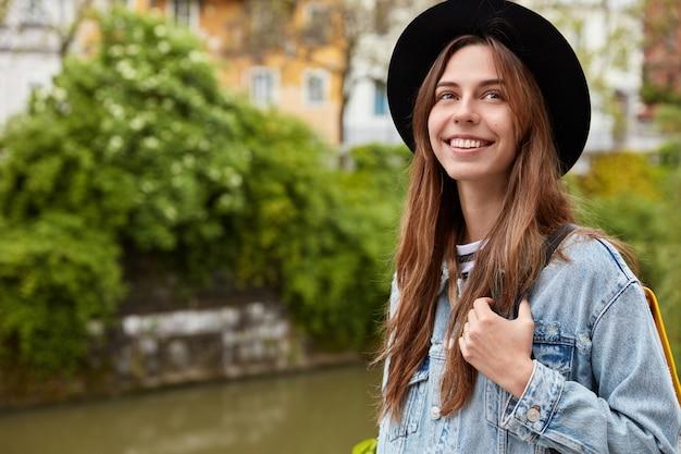 Concept de personnes et de loisirs. positive jeune femme aux cheveux noirs, porte un chapeau noir à la mode, une veste en jean, aime faire du tourisme