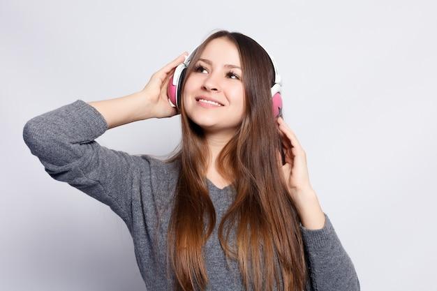 Concept de personnes, de loisirs et de technologie - femme heureuse ou adolescente dans des écouteurs écoutant de la musique à partir d'un smartphone et dansant