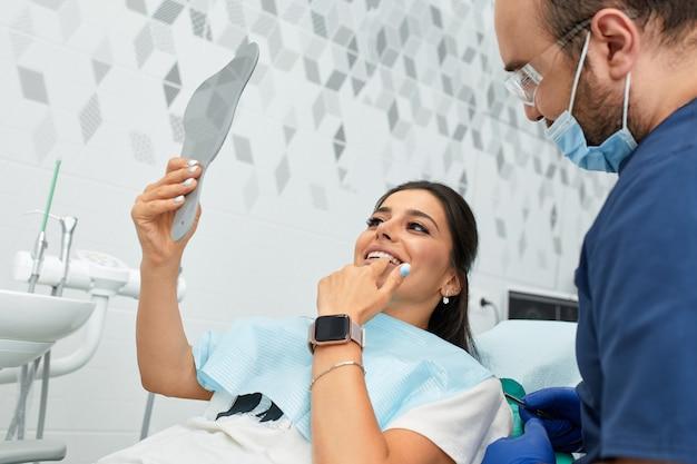 Concept de personnes, de médecine, de stomatologie et de soins de santé - dentiste masculin heureux avec une patiente au bureau de la clinique dentaire