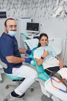 Concept de personnes, médecine, stomatologie et soins de santé - heureux dentiste masculin montrant le plan de travail à une patiente au bureau de la clinique dentaire