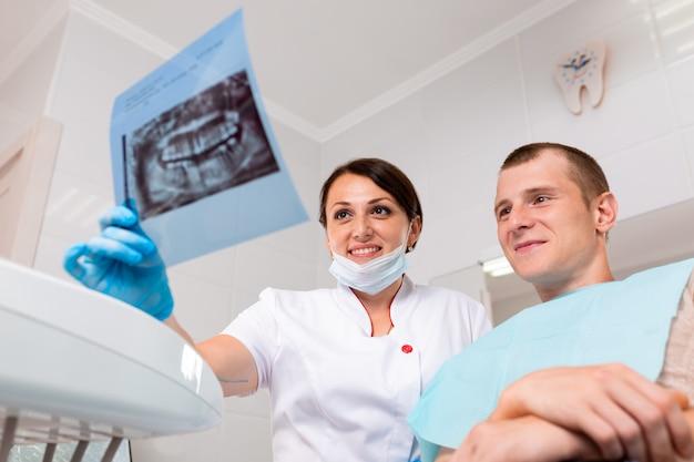 Concept de personnes, de médecine, de stomatologie, de technologie et de soins de santé - dentiste heureuse avec une radiographie des dents sur un ordinateur tablette et une patiente au bureau de la clinique dentaire