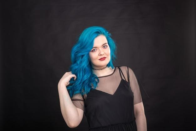 Concept de personnes et de mode - jeune et jolie femme avec rouge à lèvres noir et cheveux bleus posant