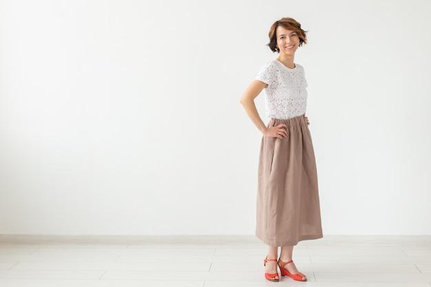 Concept de personnes, de mode et de style - jeune femme posant dans des vêtements en studio sur une surface blanche.