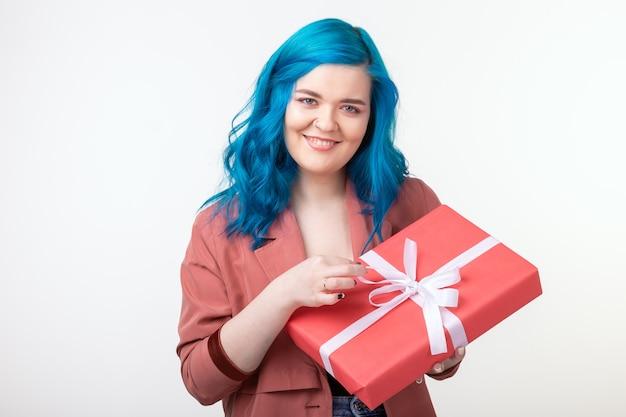 Concept de personnes, de mode et de vacances - belle fille aux cheveux bleus debout avec boîte-cadeau sur blanc