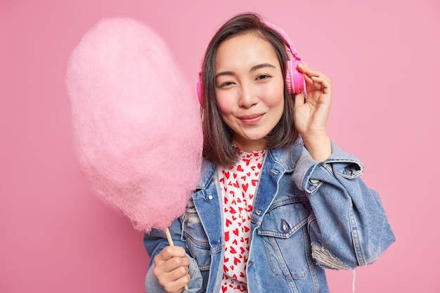 Concept de personnes et de mode de vie. une jolie adolescente asiatique écoute de la musique via des écouteurs et tient une délicieuse barbe à papa vêtue d'une veste en jean à la mode et profite de temps libre isolé sur un mur rose