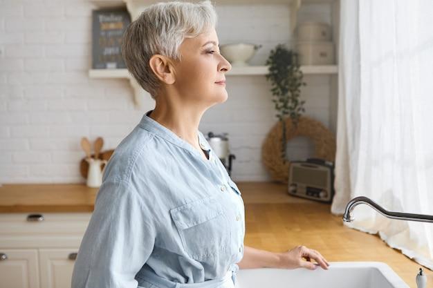 Concept de personnes, de mode de vie et de vieillissement. tir à l'intérieur de l'élégante femme à la retraite senior aux cheveux courts en robe bleue debout au lavabo blanc, regardant à travers la fenêtre, se reposer après avoir lavé toute la vaisselle