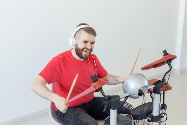 Concept de personnes, de musique et de passe-temps - homme vêtu d'un t-shirt rouge jouant sur la batterie électronique