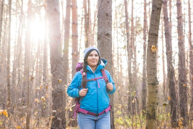 Concept de personnes et de la nature - portrait de femme avec sac à dos de randonnée dans la forêt