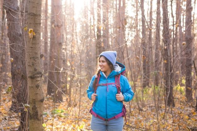 Concept de personnes et de la nature - portrait de femme avec sac à dos de randonnée dans la forêt.