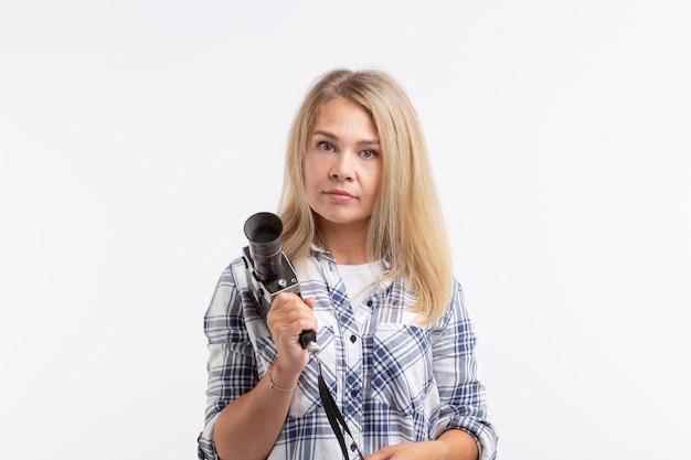 Concept de personnes, photographe et geste - femme utilisant un appareil photo à l'ancienne sur fond blanc.