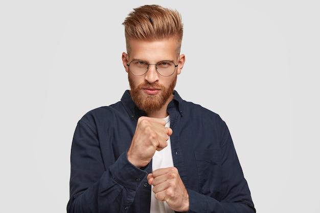 Concept de personnes et de pouvoir. homme foxy sérieux avec une expression déterminée, garde les poings serrés, regarde avec sévérité, prêt à se battre, vêtu d'une chemise bleu foncé, se dresse contre un mur blanc