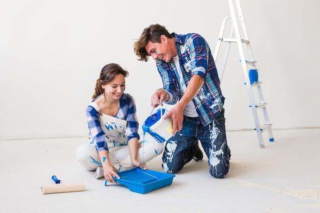 Concept de personnes, de rénovation et de réparation portrait de couple heureux verser de la peinture