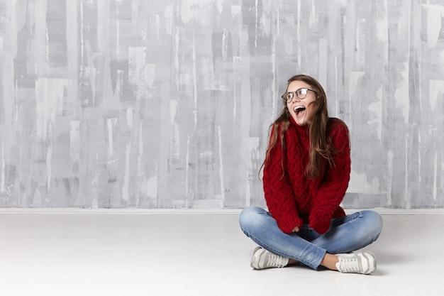 Concept de personnes, de repos et de relaxation. belle jeune femme caucasienne joyeuse en tenue élégante assise sur le sol dans sa chambre et ouvrant largement la bouche, excitée ravie de nouvelles positives