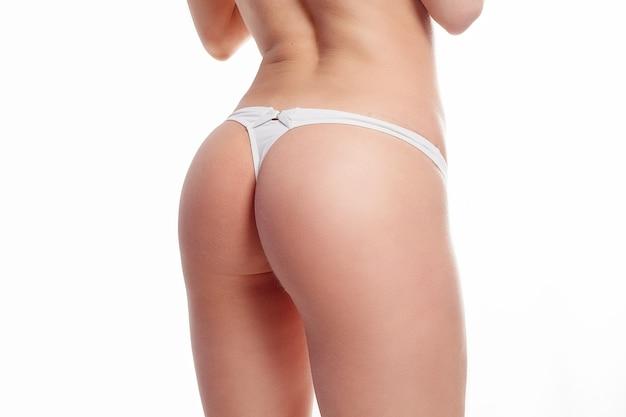 Concept de personnes, de santé et de mode de vie - beau corps de femme en forme. fille en gros plan en bonne santé avec un corps mince et ajusté, une peau douce et des fesses fermes, des hanches en culotte de bikini blanche. gros cul serré en sous-vêtements.