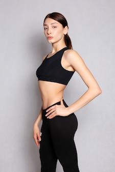 Concept de personnes, de santé et de mode de vie - fille assez en forme ou instructeur de fitness posant et souriant isolé sur fond blanc