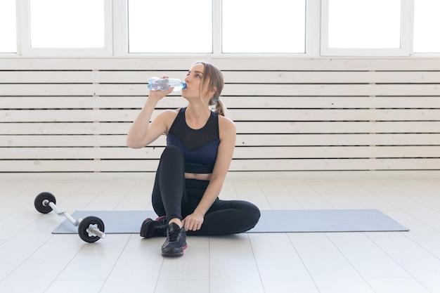Concept de personnes, de sport et de remise en forme - jeune femme buvant de l'eau de bouteille sportive alors qu'il était assis sur un tapis.